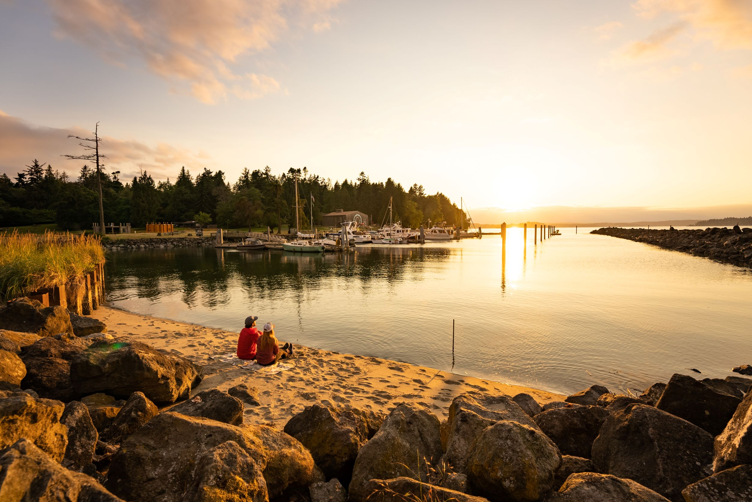 Two people sitting on beach near a boat marina with boats in midground and sunset in background