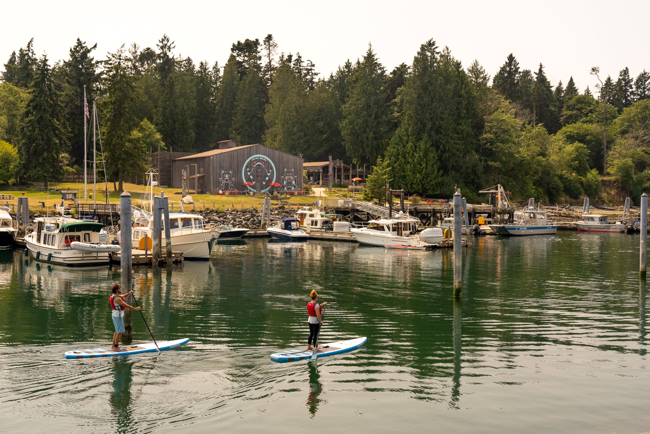 Man and woman paddle boarding in marina with boats in midground and longhouse in background with green trees surrounding it