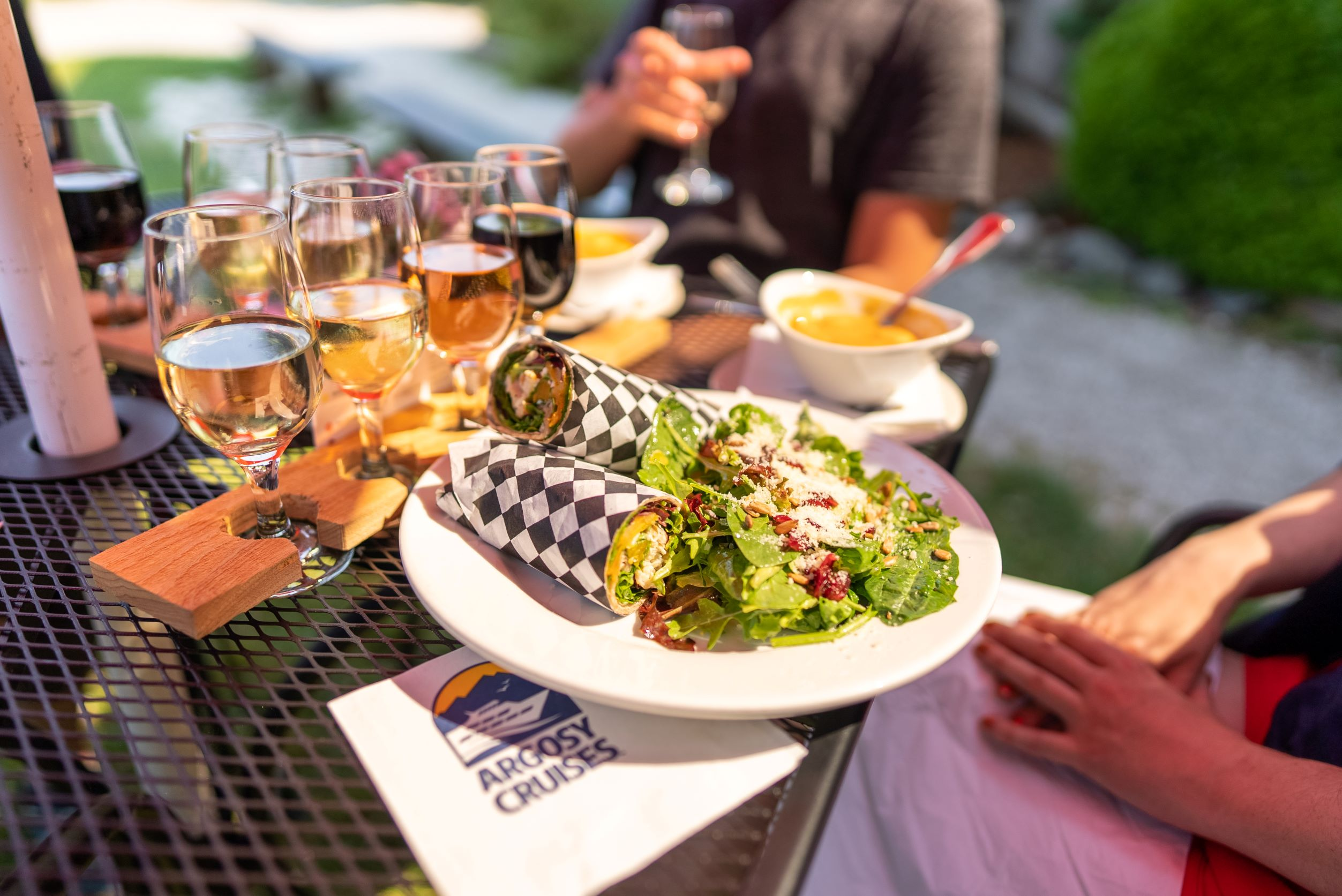 Salad and wrap on plate with wine glasses and man's hand in background
